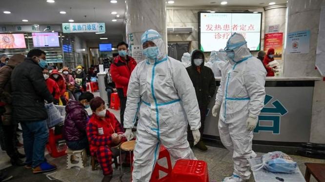 Nhân viên y tế đi bên cạnh bệnh nhân (trái) chờ chăm sóc y tế tại Bệnh viện chữ thập đỏ Vũ Hán. Ảnh: AFP