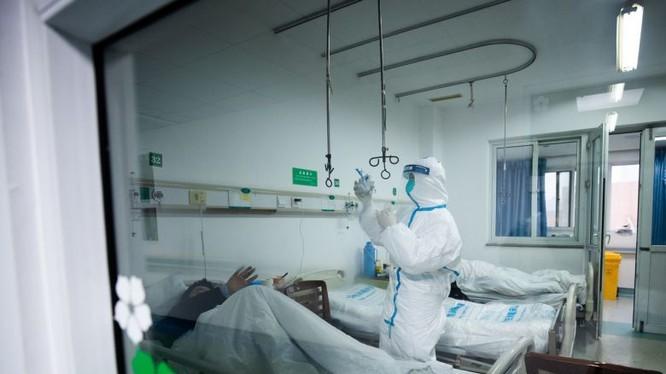 Bác sĩ chăm sóc cho bệnh nhân trong phòng cách ly. Ảnh: The straits times