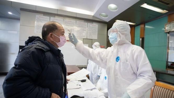 Bác sĩ đo thân nhiệt cho bệnh nhân. Ảnh: The Straitstimes