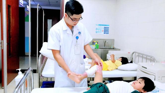Kỹ thuật viên hướng dẫn bệnh nhi bị bỏng phục hồi chức năng. Ảnh: Trung tâm Sản nhi, Bệnh viện Đa khoa tỉnh Phú Thọ