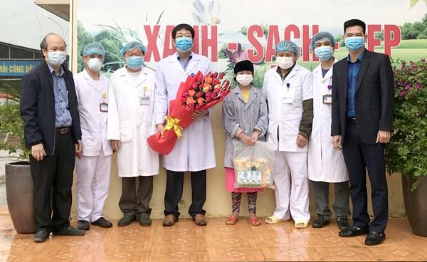 Lãnh đạo huyện Đồng Văn tặng hoa chúc mừng các y, bác sỹ và bệnh nhân 268 (đội mũ đen) được công bố khỏi bệnh vào sáng nay. Ảnh: T.N