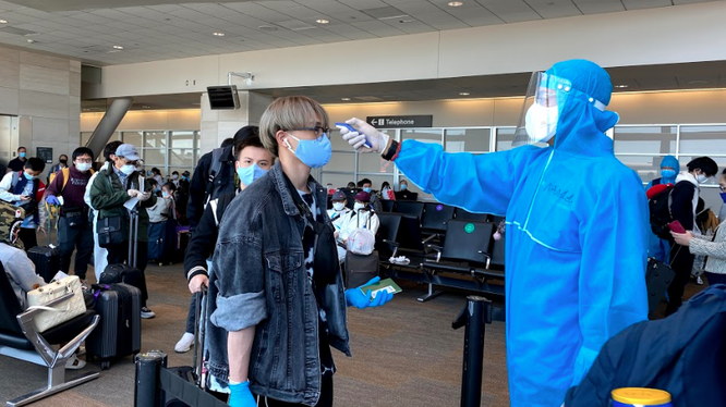 Nhân viên y tế đo thân nhiệt cho hành khách trên chuyến bay. Ảnh: BYT
