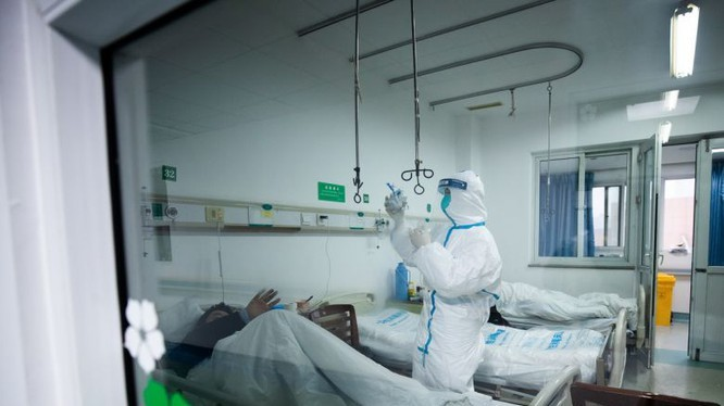 Bác sĩ chăm sóc cho bệnh nhân mắc COVID-19. Ảnh: The Straits Times.