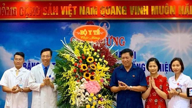 Thứ trưởng Bộ Y tế Đỗ Xuân Tuyên (áo xanh) chúc mừng em bé đầu tiên ra đời bằng kỹ thuật thụ tinh trong ống nghiệm. (Ảnh: Thảo Nguyên)