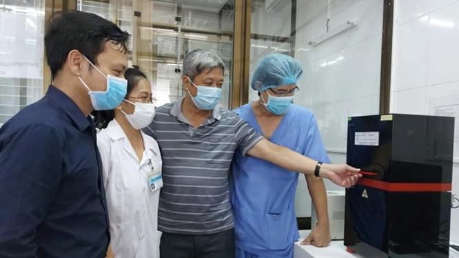 Thứ trưởng Bộ Y tế Nguyễn Trường Sơn (Áo sọc xám) tại buổi khai trương hệ thống xét nghiệm virus SARS-CoV-2 ở Bệnh viện C Đà Nẵng (Ảnh: Vũ Mạnh Cường)