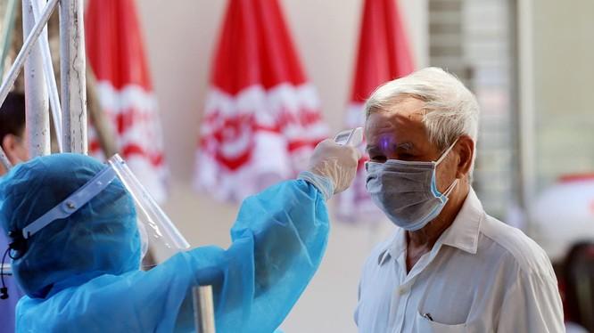 Nhân viên y tế kiểm tra nhiệt độ cho người dân (Ảnh: Bộ Y tế)