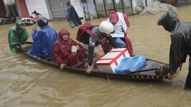 Người dân di chuyển khi nước lũ dâng cao (Ảnh: Hoàng Triều - Nguồn: baothuathienhue.vn)