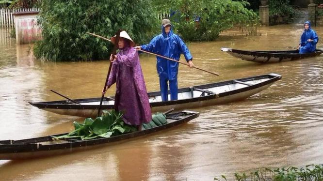 Người dân di chuyển khi thời tiết bão lũ (Ảnh: Hoàng Triều - nguồn: baothuathienhue.vn)