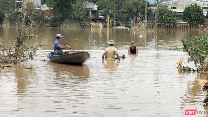 Người dân di chuyển bằng thuyền khi nước lũ dâng cao (Ảnh: Hồ Xuân Mai)