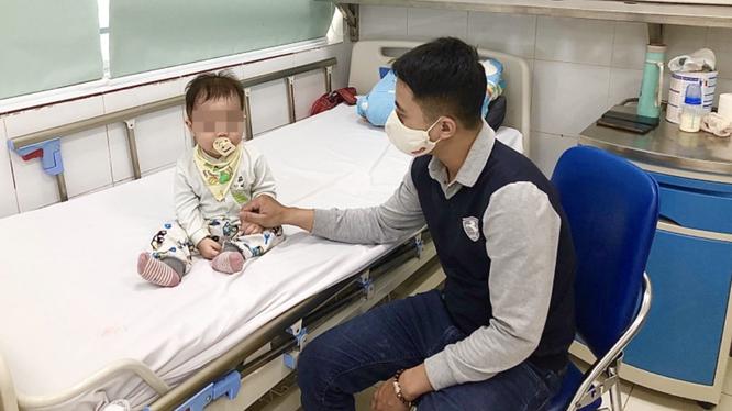 Một trẻ bị cúm được gia đình chăm sóc ở Bệnh viện Nhi Trung ương (Ảnh: BVCC)