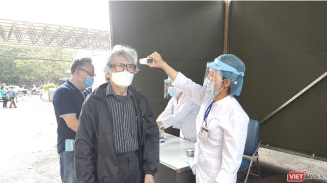 Nhân viên y tế kiểm tra nhiệt độ cho người dân (Ảnh - Minh Thuý)
