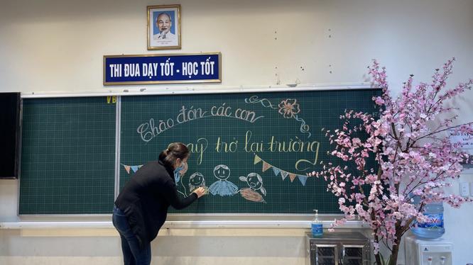 Cô giáo viết bảng chào đón học sinh quay trở lại trường (Ảnh - Phòng GD&ĐT quận Ba Đình)