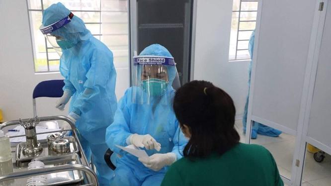 Nữ điều dưỡng Vũ Thị Thanh Thư trò chuyện với cán bộ tiêm chủng trước khi tiêm vaccine phòng COVID-19 (Ảnh: Đặng Thanh)