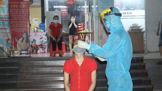 Nhân viên y tế lấy mẫu xét nghiệm COVID-19 cho người dân (Ảnh - TNTV)