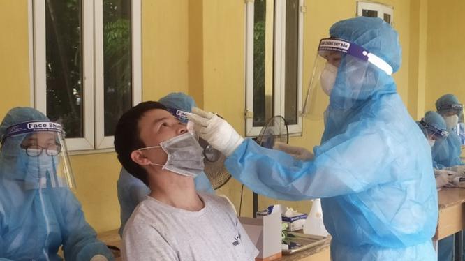 Nhân viên y tế lấy mẫu xét nghiệm COVID-19 cho người dân (Ảnh - SYTHN)