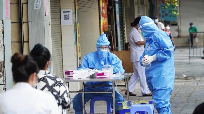 Nhân viên y tế lấy mẫu xét nghiệm COVID-19 cho người dân ở khu vực bên ngoài Bệnh viện Hữu nghị Việt Đức (Ảnh - Minh Nhân)