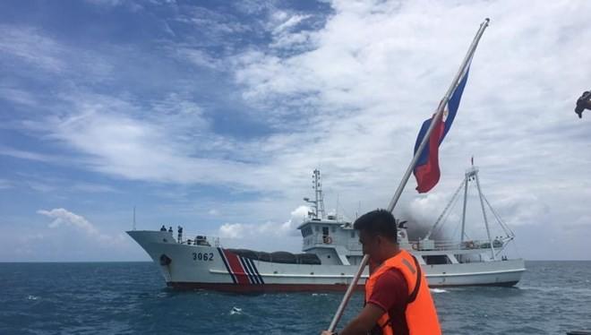 Một thành viên của nhóm Kalayaan Atin Ito đang thực hiện cắm quốc kỳ Philippines trên bãi cạn Scarborough nhưng bị Trung Quốc cản trở.
