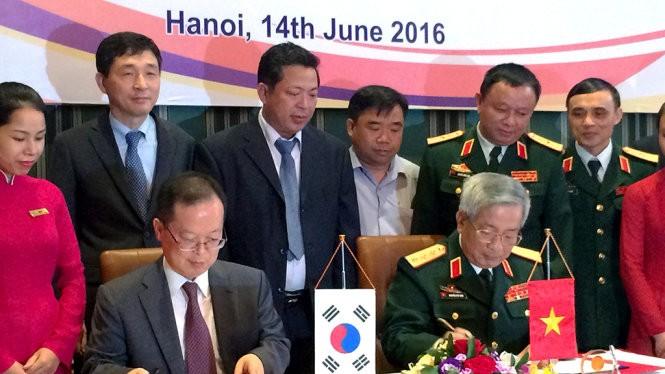 Thượng tướng Nguyễn Chí Vịnh (phải) và ông Chang Jae Yun ký kết biên bản hợp tác khắc phục hậu quả bom mìn sau chiến tranh - Ảnh: Q.TR..