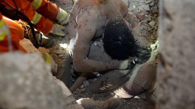 Hình ảnh người cha công nhân dùng thân mình che chắn cho con gái gây xúc động mạnh - Ảnh: AFP.
