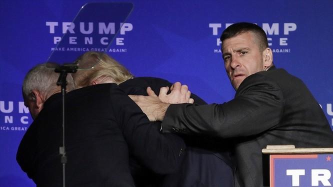 Donald Trump bị một phen hú hồn, phải chạy vào sau sân khấu dưới sự yểm trợ của nhân viên an ninh.