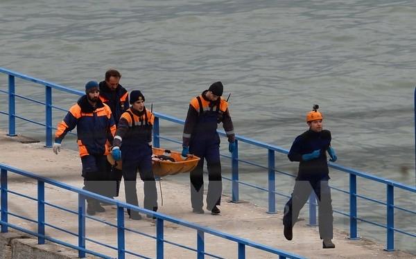 Các nhân viên cứu hộ đưa thi thể nạn nhân vào bờ. (Nguồn: THX/TTXVN)