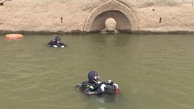 Các chuyên gia khảo cổ học của Trung Quốc mặc đồ thợ lặn nghiên cứu bức tượng - Ảnh: CCTV