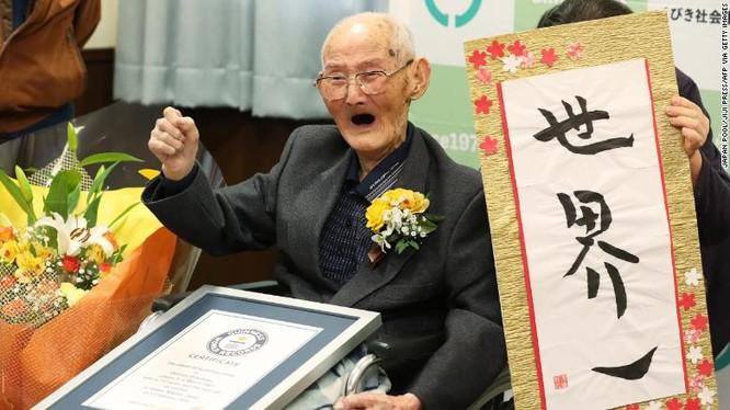 """Người đàn ông Nhật Bản 112 tuổi, Chitetsu Watanabe, đứng bên cạnh tờ thư pháp bằng tiếng Nhật """"Số 1 thế giới"""" sau khi ông được công nhận là người đàn ông sống lâu nhất thế giới ở Joetsu, quận Niigata vào ngày 12/2."""