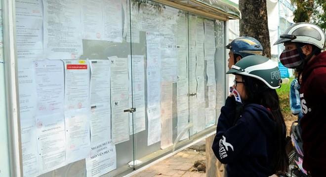 Người tìm việc, công nhân đang xem thông báo tuyển dụng đặt trong khuôn viên Khu công nghiệp Amata (P.Long Bình, TP Biên Hòa, Đồng Nai) ngày 9-3