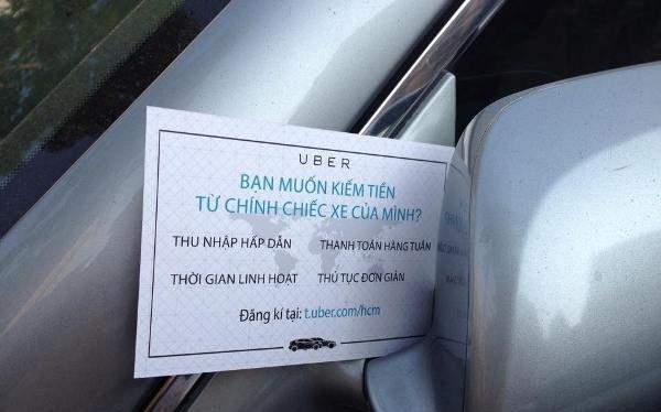 Một mẩu quảng cáo của Uber gắn trên kiếng xe chiếu hậu của chủ một xe hơi ở TPHCM