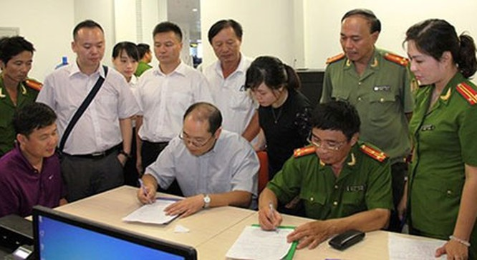 Đối tượng Yin Wen Sheng (áo tím) cùng hồ sơ, tài liệu được cơ quan chức năng Việt Nam bàn giao cho phía Trung Quốc.
