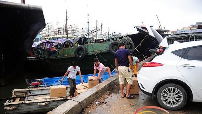 Ngư dân cảng Tam Á, Hải Nam, chất lương thực lên thuyền con, chở ra ngoài tàu lớn. Ảnh: HiNews