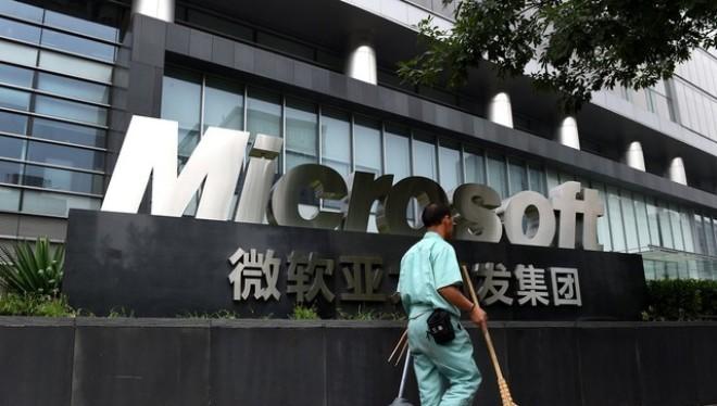 Một công nhân đi ngang qua văn phòng Microsoft tại Bắc Kinh (Ảnh: Bloomberg)