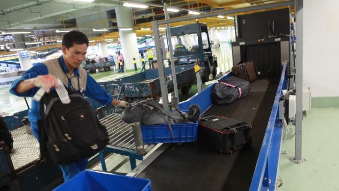 Hành lý ký gửi từ máy bay đến được đưa vào băng chuyền ra đảo hành lý tại cảng hàng không Nội Bài