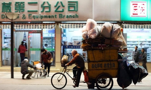 Một người đàn ông đang đạp xe qua một khu phố mua sắm tại Bắc Kinh. Ảnh:Bloomberg