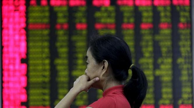 Một nhà đầu tư đăm chiêu theo dõi giá cổ phiếu trên một bảng điện tử tại Bắc Kinh - Ảnh: Reuters