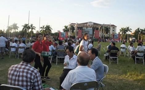 Người dân đến với lễ hội bia, nhận bia lon rồi ngồi xuống bãi cỏ sân vận động, uống.