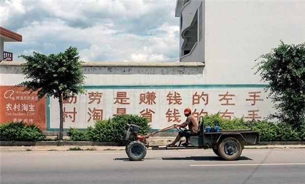"""Quảng cáo với nội dung: """"Tay trái siêng năng kiếm tiền, tay phải tiết kiệm với Taobao nông thôn"""". Ảnh: Bloomberg"""