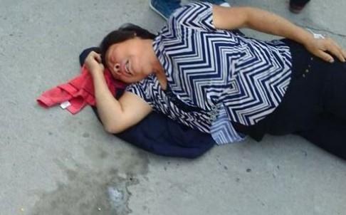 Một người phụ nữ ngã lăn ra sau khi hít phải khí độc. Ảnh: SCMP