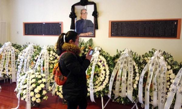 Một người phụ nữ chụp ảnh các vòng hoa của ông Tập và lãnh đạo CPC viếng tang ông Tăng Vân Tiếu