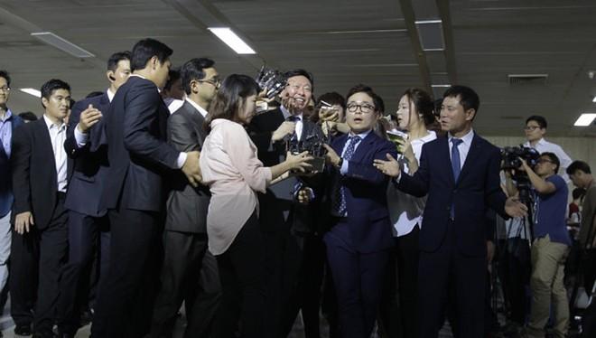 Ông Shin Dong Bin (giữa) trong vòng vây phóng viên sau khi hoàn toàn nắm quyền kiểm soát tập đoàn Lotte. Ảnh: AFP