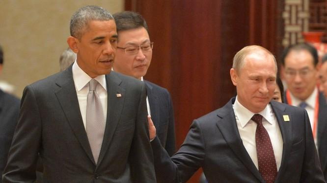 Tổng thống Nga chạm vai ông Obama khi tham dự phiên họp toàn thể của Hội nghị Thượng đỉnh châu Á - Thái Bình Dương tại Trung tâm Hội nghị quốc tế ở Bắc Kinh ngày 11/11/2014. Ảnh: AFP