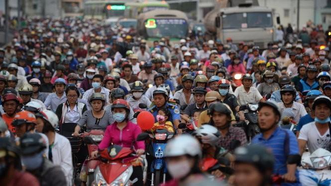 Với nhiều người nghèo, việc thu phí xe máy là một gánh nặng. Trong ảnh: người dân chen chúc đi xe qua cầu Chà Và, Q.8, TP.HCM - Ảnh: Thuận Thắng
