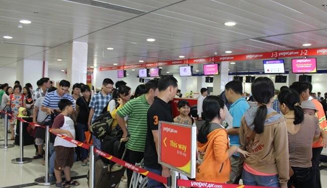 Hành khách xếp hàng dài chờ đợi làm thủ tục tại sân bay Tân Sơn Nhất - Ảnh: Anh Quân