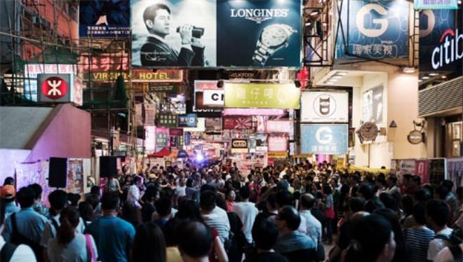 Du khách trên đường phố ở quận Mong Kok của Hồng Kông - Ảnh: Bloomberg