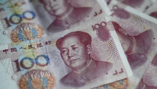 Đồng tiền giấy mệnh giá 100 NDT (15.5 USD) tại Bắc Kinh ngày 25/8 vừa qua. (Ảnh: AFP/TTXVN)