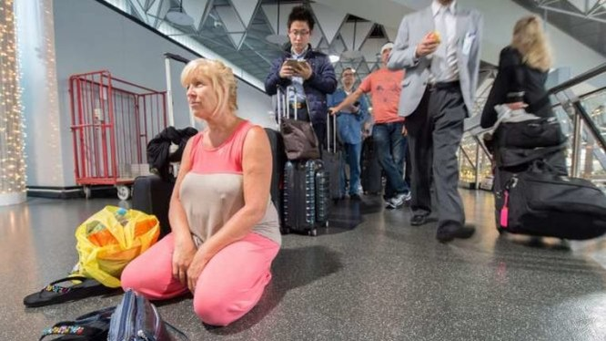 Một hành khách đang mệt mỏi chờ chuyến bay về Hawaii tại sân bay quốc tế ở Frankfurt, Đức hôm 8-11 - Ảnh: EPA
