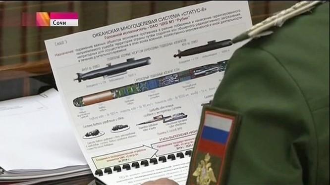 Hình ảnh tướng Andrei Kartapolov cầm tài liệu in rõ hệ thống vũ khí hải quân Status 6 của Nga đang được lan truyền trên mạng. Phía trên bên trái là tàu ngầm hạt nhân lớp 09852 mang dưới bụng 1 tàu ngầm không người lái, bên phải là tàu ngầm hạt nhân lớp 09