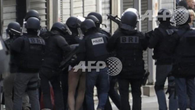Cảnh sát Pháp dẫn giải một kẻ bị bắt trong cuộc đột kích vào căn hộ ở St Denis (Nguồn: AFP)