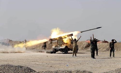 Các tay súng Shiite phóng rốc két về phía mục tiêu của tổ chức Nhà nước Hồi giáo (IS) tự xưng ở TP Baiji - Iraq Ảnh: REUTERS