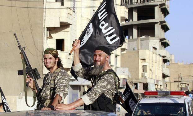 Các tay súng của IS giương cờ khi đi lại trên đường phố Raqqa, Syria. Ảnh: Reuters